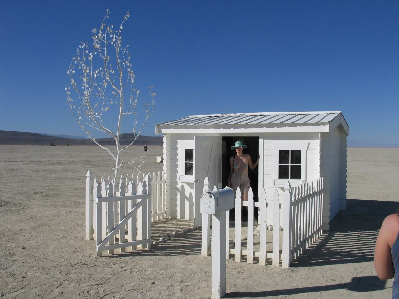 a small home with picket fence out in the deep desert complete with mailbox full of gifts brads photos